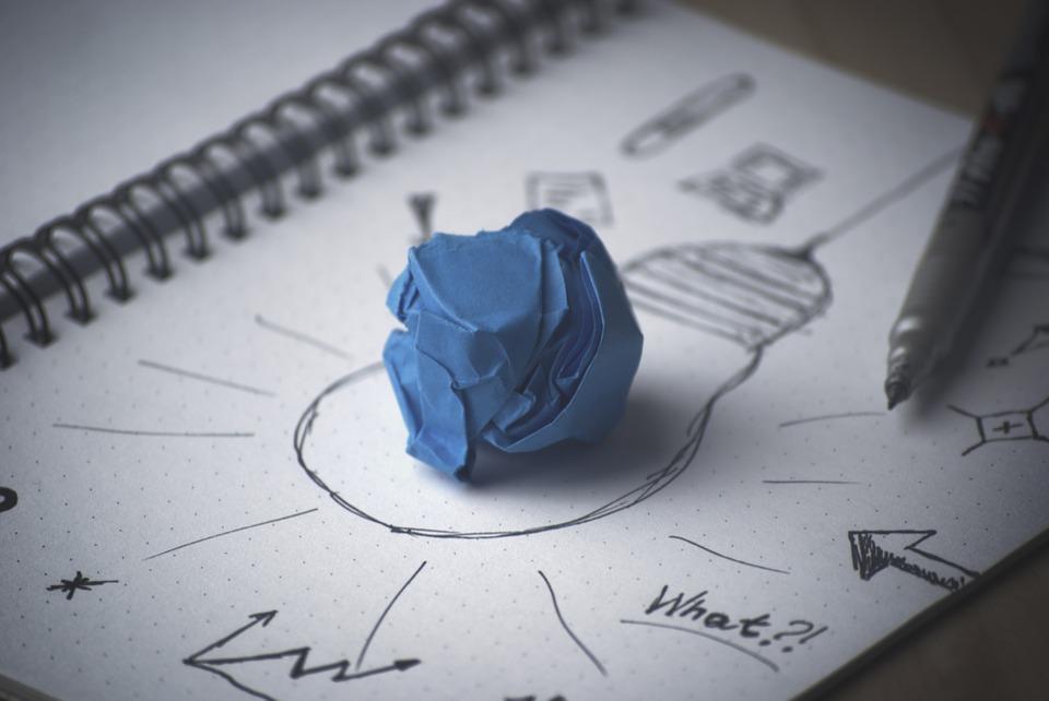 Bozza, foglio con varie scritte, lampadina accesa. Creatività e innovazione.